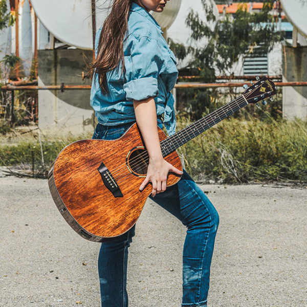 woman facing away from camera holding acoustic guitar outside