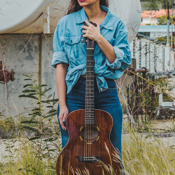woman holding Washburn acoustic guitar outside