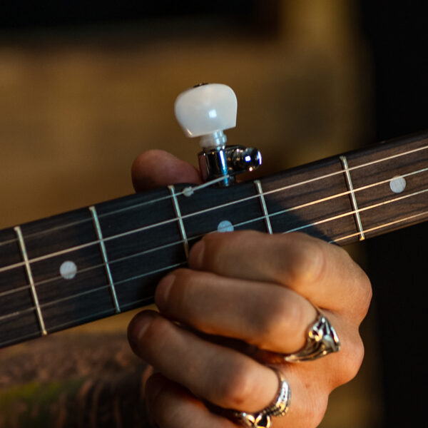 closeup of man's hand on banjo fret