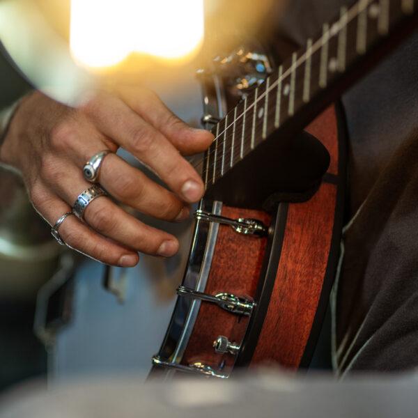 hand of man playing banjo