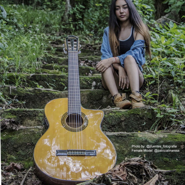 girl sitting behind Washburn acoustic guitar on outdoor steps