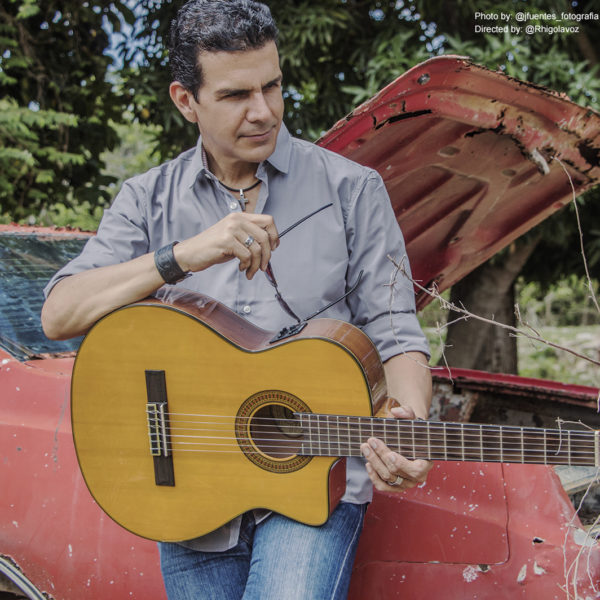 male musician leaning on red car holding Washburn acoustic guitar