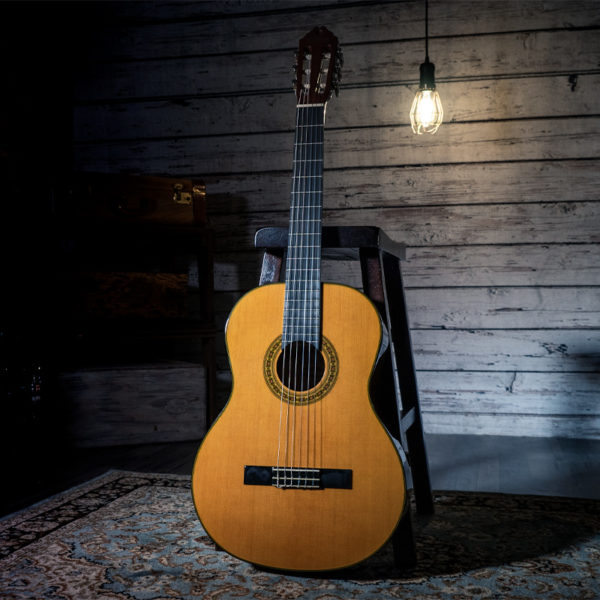Washburn classical guitar leaning on stool