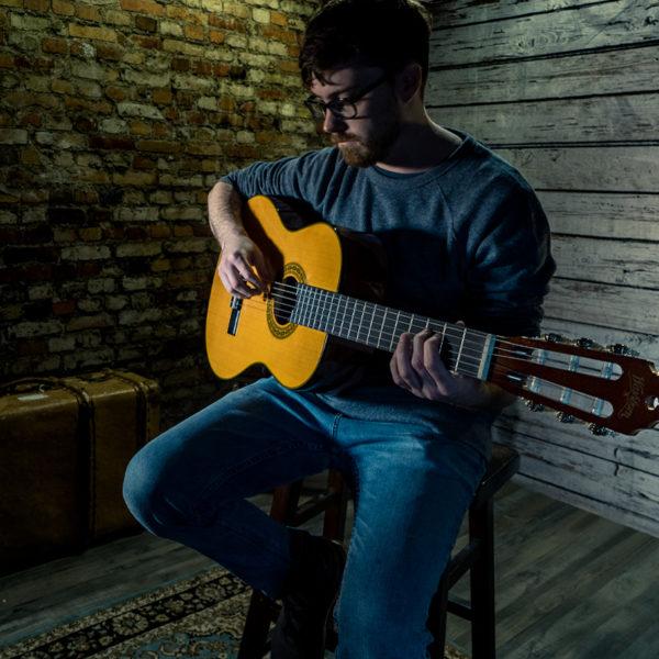 man playing Washburn acoustic guitar