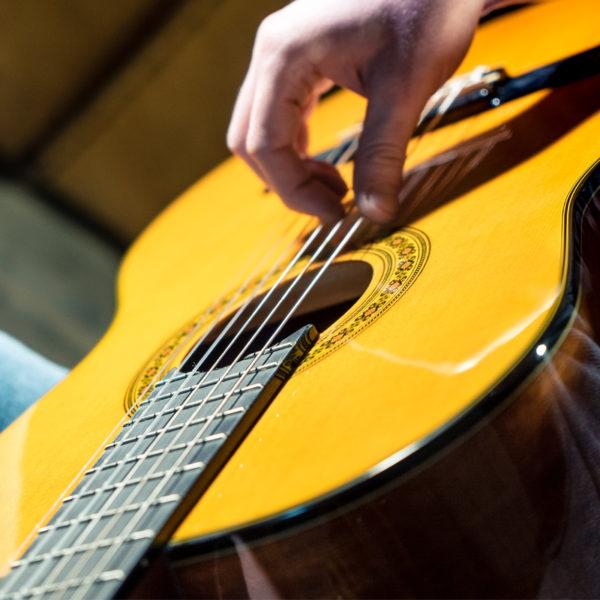 hand strumming Washburn classical guitar