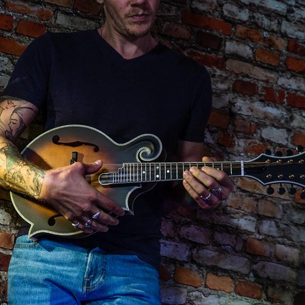 partial view of man in front of brick wall playing Washburn mandolin