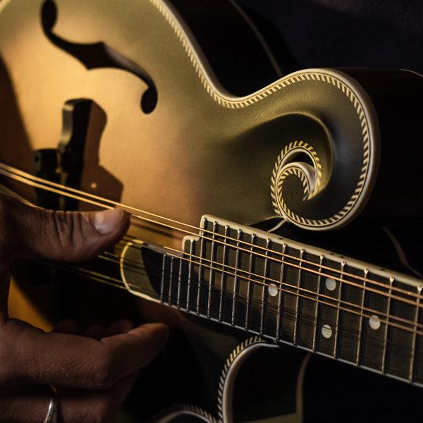 closeup of man's hands playing Washburn mandolin