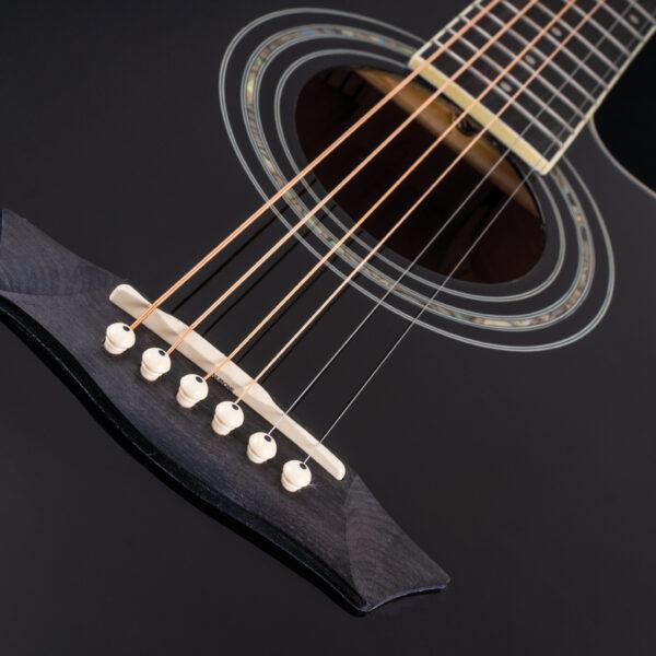 closeup of body of black acoustic guitar