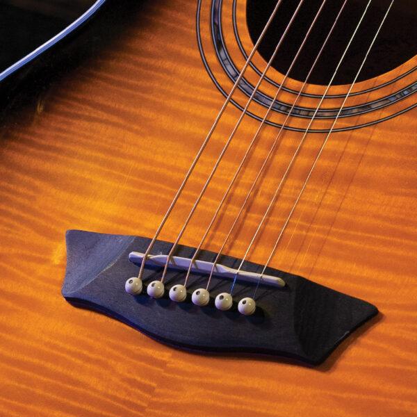 closeup of bridge on yellow acoustic guitar