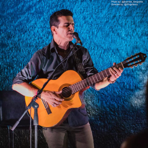 male musician playing Washburn classical guitar and singing in concert