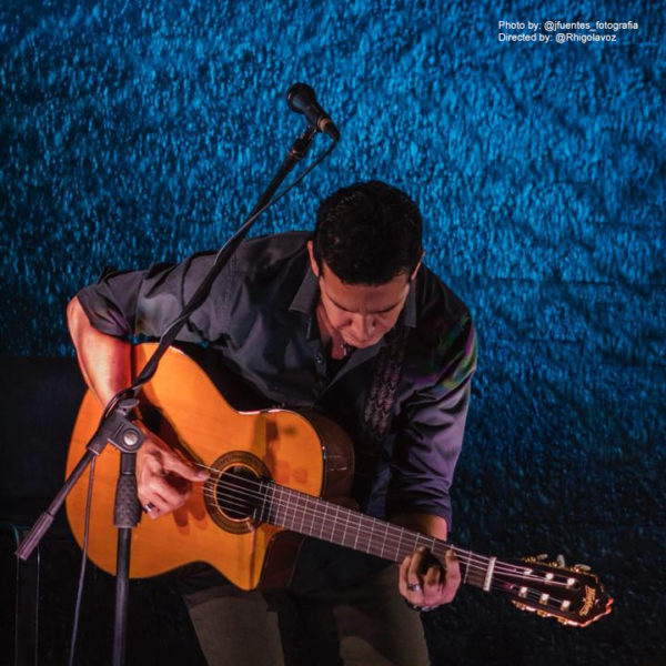 male musician playing Washburn classical guitar
