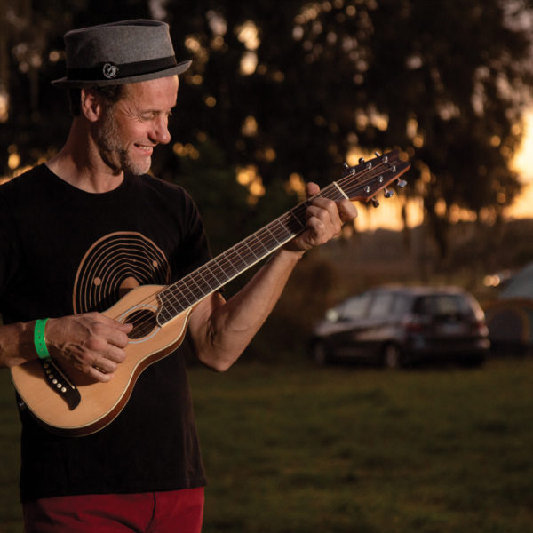 Artist playing RO10SK Rover Travel Guitar at a campsite