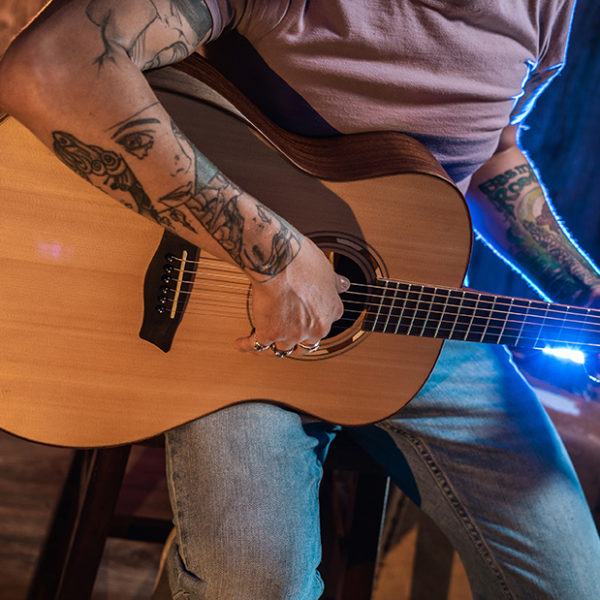 partial view of man holding Washburn acoustic guitar
