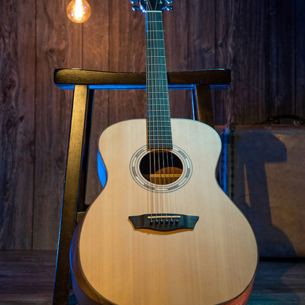 Washburn acoustic guitar leaning against stool