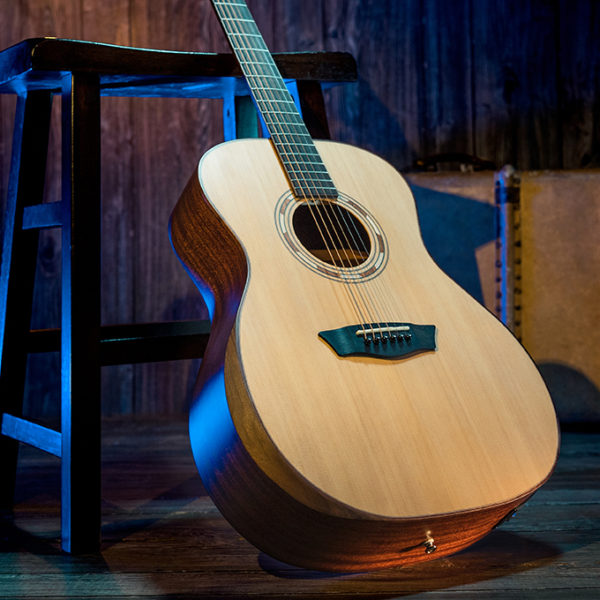 Washburn acoustic guitar leaning up against stool