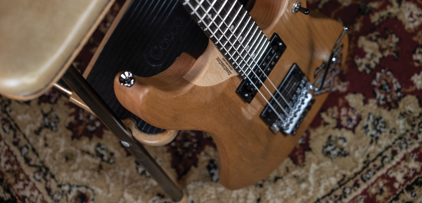 4N NUNO BETTENCOURT SIGNATURE USA partial view of guitar leaning on vintage chair