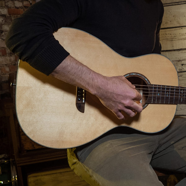 partial view of man playing Washburn acoustic guitar