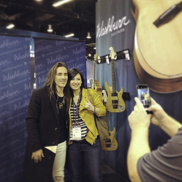 woman posing for picture with musician at Washburn event
