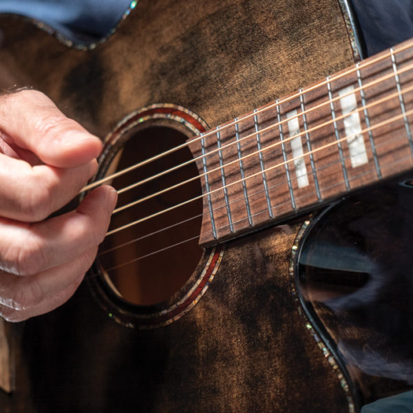 hands of man playing Washburn acoustic guitar